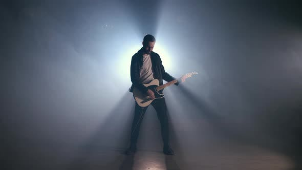 Thumbnail for Rock Guitarist Man on Smoky Stage and Masterfully Playing Electric Guitar.
