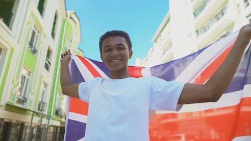 Glad Mixed-Race Young Guy Waving British Flag and Smiling, National Holiday