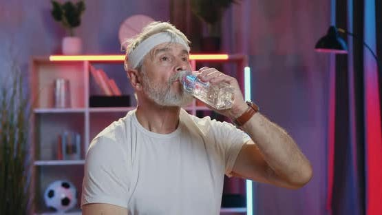 Old Bearded Man in white T-Shirt and White Headband which Refreshing with Water from Bottle