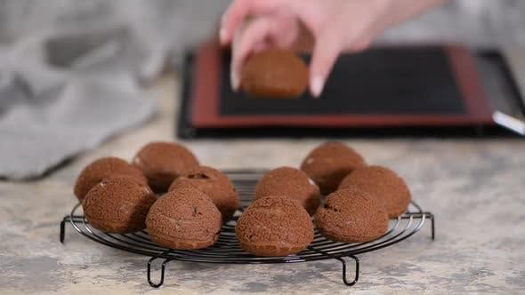 Frisch gebackene Schokoladen-Profiteroles auf Kühlregal.
