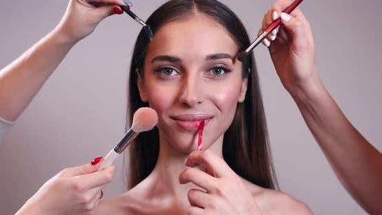 Multiple Hands Doing Make Up of Young Woman