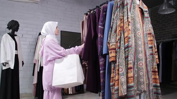 A Young Muslim Woman Choosing Clothes at the Store