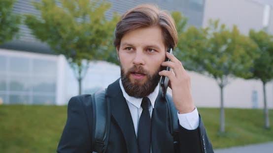 Thumbnail for Bärtiger Office-Manager mit Rucksack, der Telefongespräche hat