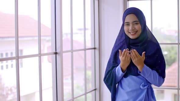 Asian Muslim young woman in traditional hijab is praying glorify Allah