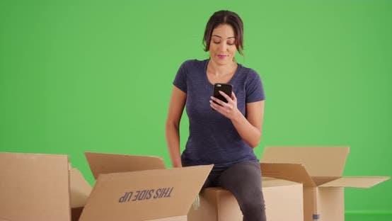 Frau sitzt auf Umzugskartons Nachricht jemand auf Handy auf grünem Bildschirm
