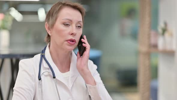 Professional Middle Aged Female Doctor Talking on Smartphone