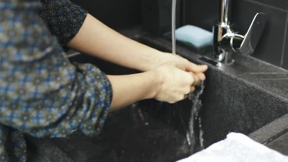 Woman wipes hands with dry towel after washing hands