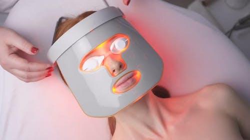 Frau beim Kosmetiker erhält eine kosmetische Hardware-Prozedur der Photoporation.
