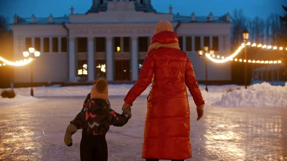 Thumbnail for A Family of Mother and Two Kids Skating on Public Ice Rink at Evening in Bright Lights - Back View