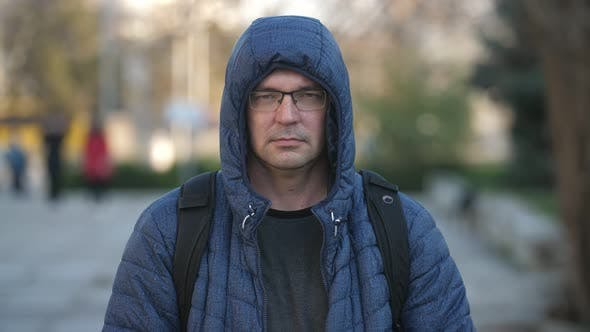 Cover Image for Middle-aged Man in Eyeglasses, a Jacket with a Hood Smiling on a Street in Fall