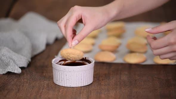 Koch schmückt Kekse mit geschmolzener Schokolade.