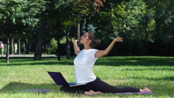 Thumbnail for Girl Has a Yoga Practice in the Park with Laptop