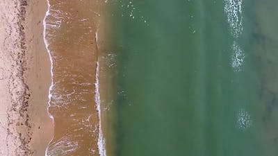 Vertical orientation video: Small sea waves. Soft waves on a sandy beach. Seascape background