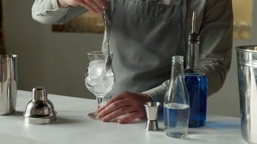 Professional Man Bartender Stirring Ice in the Glass on the Bar Counter
