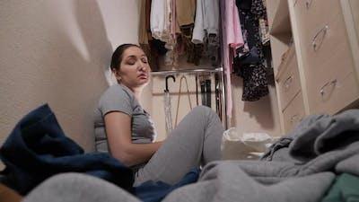 Upset Maid Looks at Dirty Laundry on Floor in Walkin Closet