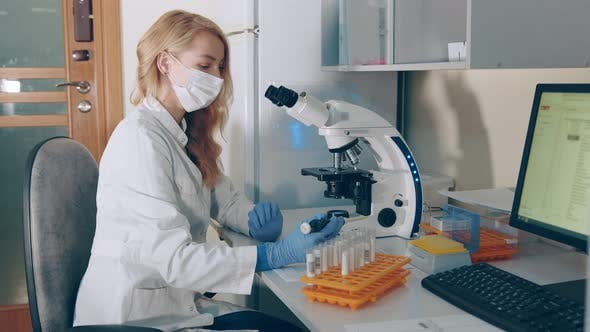 Thumbnail for Microbiologist Works with a Microscope in a Laboratory and Research Center. A Woman of Caucasian