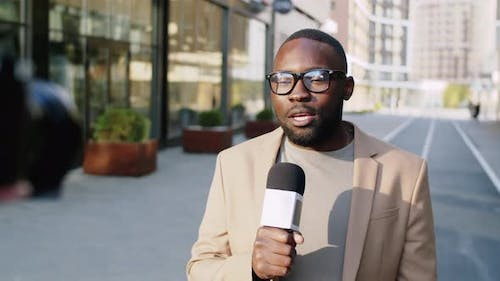 Afro-American Male Reporter Telling News at Camera Outdoors