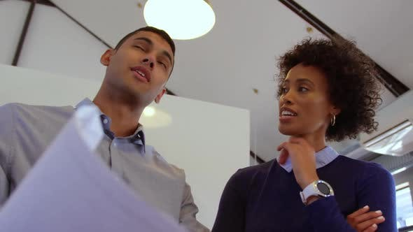 Thumbnail for Mixed-race business people discussing over blueprint in a modern office 4k