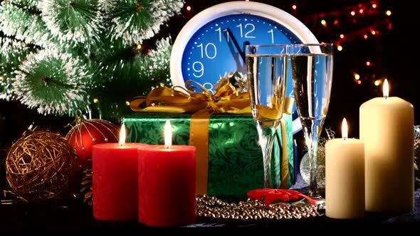 Thumbnail for Glasses with Champagne on New Year Eve Against Wall Clock, Candles, Presents, Bokeh, Garland, on