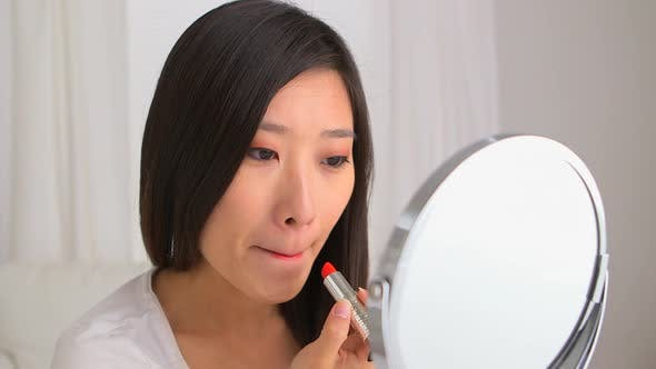 Thumbnail for Chinese woman putting on lipstick