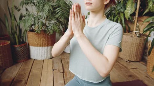 Midsection of Woman Sitting with Hands in Namaste and Practicing Yoga
