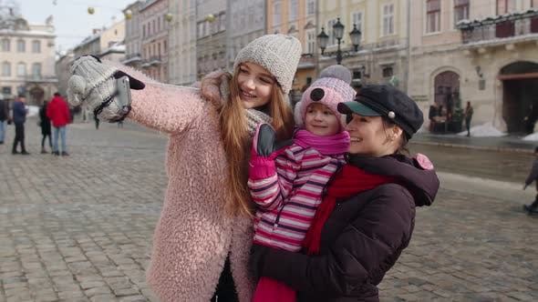 Lesbian Couple Tourists with Adoption Child Girl Taking Selfie or Making Video Chat on City Street