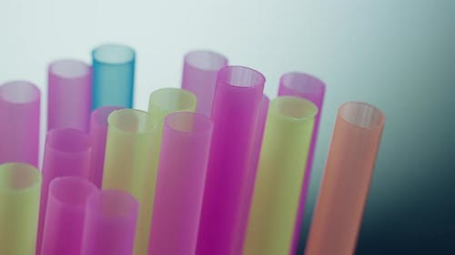 Multicolored plastic cocktail straws, close-up, camera movement