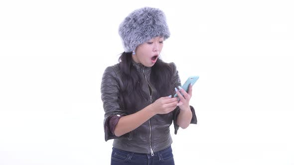 Thumbnail for Happy Beautiful Asian Woman Using Phone and Looking Surprised