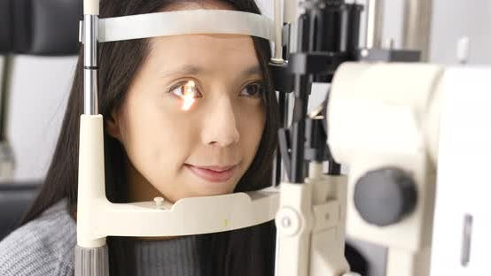 Cover Image for Young asian woman doing eye test