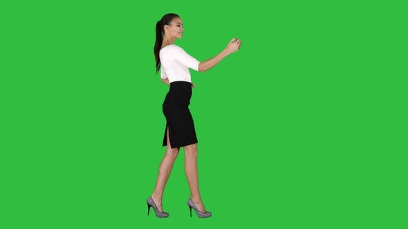 Thumbnail for Pretty girl taking a selfie and walking on a Green Screen