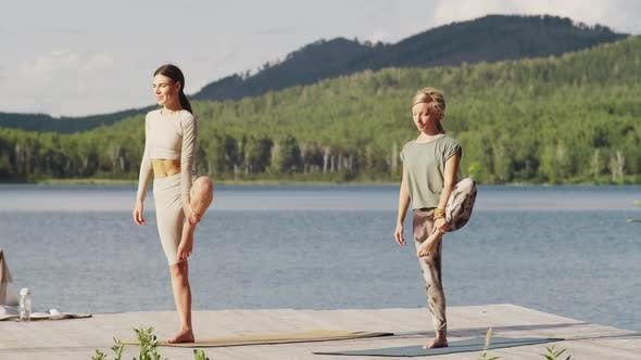 Two Women Standing in Tree Pose during Outdoor Yoga Practice