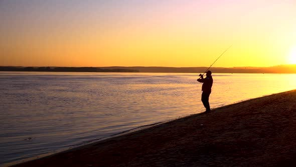 A Man Is Fishing at Sunrise By the River. The Yellow Sun Rises From the Horizon, Silhouette
