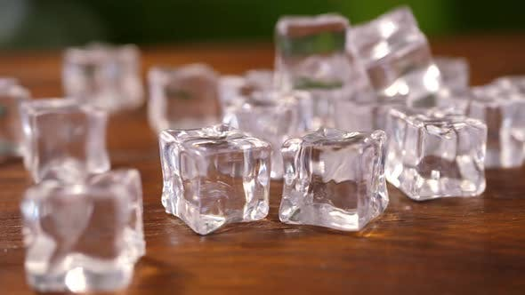 Ice Cubes on Brown Wooden Background
