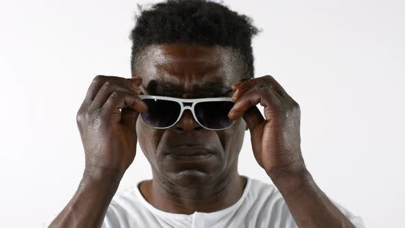 Thumbnail for Confident African Man Putting on Sunglasses