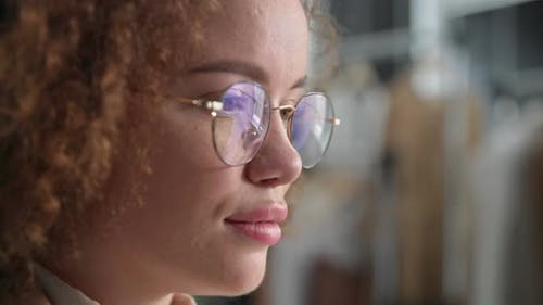 Portrait of a Young Woman with Glasses for Vision Uses Modern Technologies and Looks at the Screen