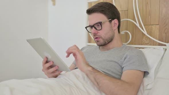 Thumbnail for Verärgert Bart junge Mann erhalten schockiert auf Tablette im Bett