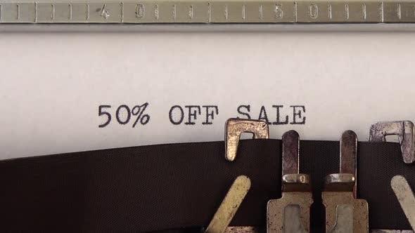 Typing phrase 50% OFF SALE on retro typewriter. Close up.