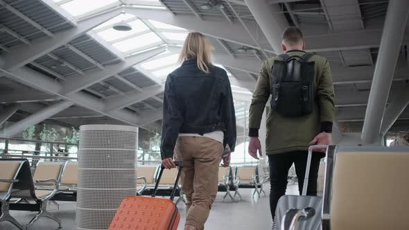 Airport Passengers Rolling Their Luggage