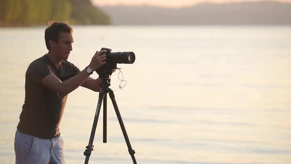 A professional photographer setting up his camera on tripod to document the beauty of nature