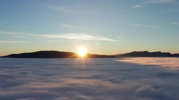 Thumbnail for Dramatic sunrise in mountains with low clouds covering valley from aerial view