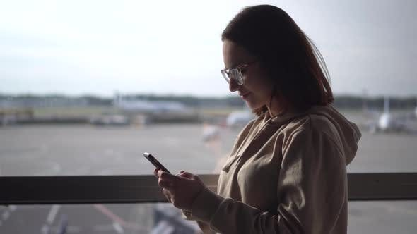 Thumbnail for Young Woman with a Phone in Her Hands on the Background of a Window at the Airport Closeup