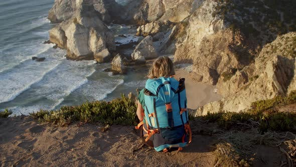 Back View of Female Tourist with Backpack Sitting at Cliff