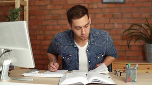 Front View of Focused Young Male College University Student Studying Preparing for Exam Taking