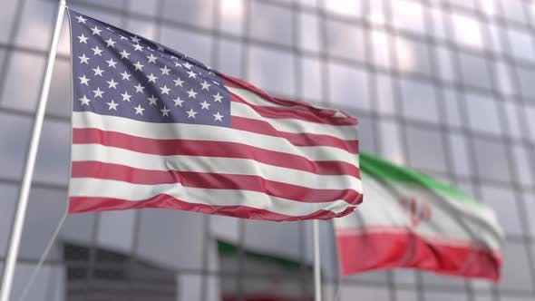 Waving Flags of the USA and Iran in Front of a Skyscraper