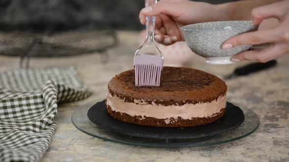 Thumbnail for Unrecognizable female confectioner hand soaks sponge cake with sweet coffee
