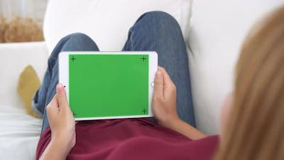 Young asian woman using black tablet device with green screen. Asian woman holding tablet.