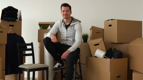 Thumbnail for A Happy Moving Man Sits on a Chair and Smiles at the Camera in an Empty Apartment