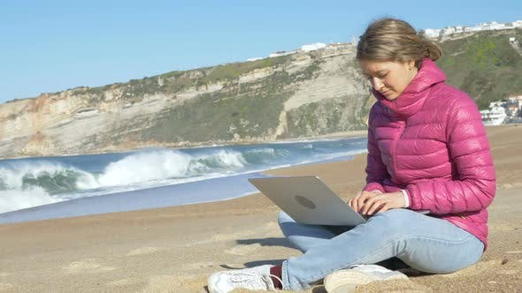 Thumbnail for Freelancer Sits on Ocean Beach Sand with Laptop and Works
