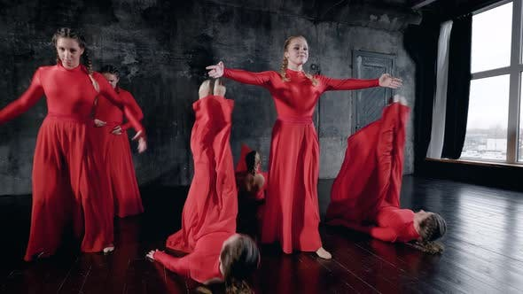 Thumbnail for Group of Young Dancers Girls Are Wearing Long Red Dresses Are Rehearsing in Dark Hall Performing