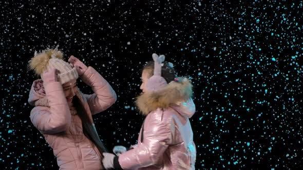 Thumbnail for Erster Schnee. Glückliche Familie freut sich und Umarmungen auf einem schwarzen Hintergrund im Studio. Schneit. Schneeflocken